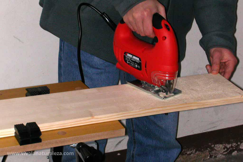Cortando las piezas de madera de la casa para aves silvestres
