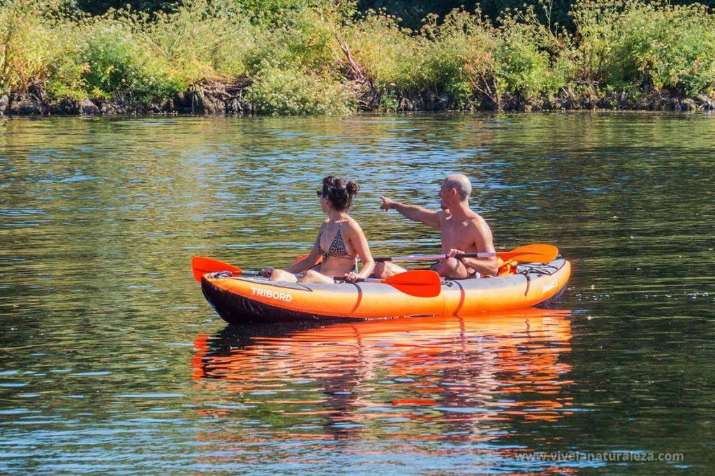 Una pareja disfruta de la naturaleza haciendo piragüismo en un río
